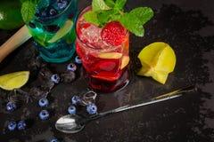 Ljusa coctailar med mintkaramellen, limefrukt, is, bär och carambolaen på den svarta bakgrunden Uppfriskande sommardrycker kopier Fotografering för Bildbyråer