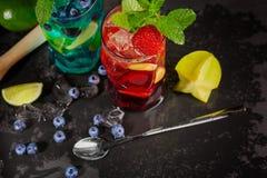 Ljusa coctailar med mintkaramellen, limefrukt, is, bär och carambolaen på den svarta bakgrunden Uppfriskande sommardrycker kopier Arkivfoto