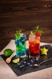 Ljusa coctailar med mintkaramellen, limefrukt, is, bär och carambolaen på den svarta tabell-servetten Uppfriskande sommardrycker  Arkivfoton