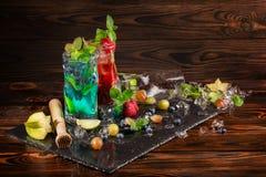 Ljusa coctailar med mintkaramellen, limefrukt, is, bär och carambolaen på det svarta skrivbordet Kalla sommardrycker för partier  Arkivbild
