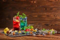 Ljusa coctailar med mintkaramellen, limefrukt, is, bär och carambolaen på träbakgrunden Sommardrycker kopiera avstånd Royaltyfria Foton