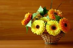 Ljusa dekorativa konstgjorda blommor i en vävd korg för ditt skrivbord arkivbilder