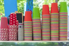 Ljusa disponibla koppar på räknaren av ett utomhus- kafé Pappers- koppar för olika drinkar royaltyfria foton