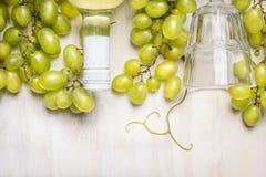 Ljusa druvor med en flaska av vitt vin och exponeringsglas på lantligt en vit träbakgrund royaltyfri foto