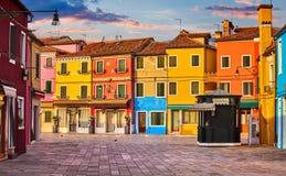 Ljusa färgade hus på den Burano ön Venedig Italien med blå himmel och moln Royaltyfri Bild
