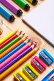 Ljusa färgpennor, markörer och vässare tillsammans med en anteckningsbok på tabellen fotografering för bildbyråer