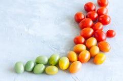 Ljusa färgrika tomater som är körsbärsröda på en vit stenbakgrund Ove Arkivbild