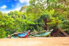 Ljusa fartyg på den tropiska stranden av Bentota, Sri Lanka på en solig dag Royaltyfri Bild