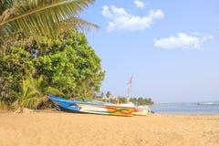 Ljusa fartyg på den tropiska stranden av Bentota, Sri Lanka på en solig dag Arkivfoton