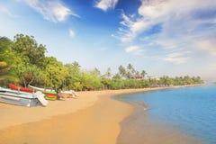 Ljusa fartyg på den tropiska stranden av Bentota, Sri Lanka på en solig dag Royaltyfri Foto