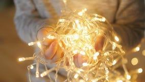 Ljusa girlander i händerna av ett barn arkivfilmer