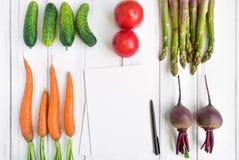 Ljusa grönsaker och en kokbok på vit bakgrund Sund mat för sallad Lekmanna- lägenhet, bästa sikt, sikt från över arkivfoto