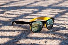 Ljusa gula exponeringsglas med en svart ram och mång--färgade linser ligger på sanden i skuggan av rastret I reflexion vara Arkivfoto