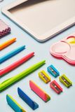 Ljusa gummi, vässare och pennor på en blå tabell royaltyfria bilder