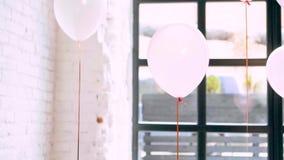 Ljusa heliumballonger i rosa vita färger hänger över golvet, medan genomskinliga underbara ballonger ligger på golvet lager videofilmer