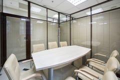 Ljusa kontorsrullgardiner som stängs med en tabell Arkivfoto