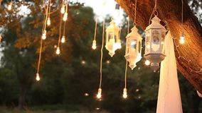 Ljusa kulor för dekorativ antik edison stilglödtråd som hänger i träna, glass lykta, lampgarneringträdgård på arkivfilmer