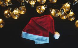 Ljusa kulor och Santa Hat på svart trä Top beskådar royaltyfri bild