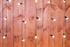 Ljusa kulor på träbakgrund Girland tappningedison för ljusa kulor i vindinre Royaltyfria Bilder
