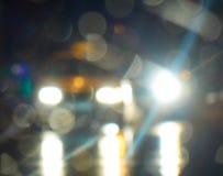 Ljusa ljus från bilar på den oskarpa abstrakta bakgrunden för nattstadsgata royaltyfria bilder