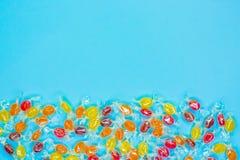 Ljusa mångfärgade godisar i omslag av genomskinlig glimmer, sötsaker på blå bakgrund, den färgrika godisen spridde, den bästa sik arkivbild
