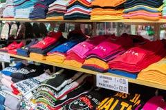 Ljusa Malta t-skjortor på hyllor Arkivbild