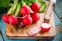 Ljusa nya organiska rädisor med skivacloseupen på skärbräda Royaltyfri Foto