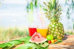 Ljusa nya sunda fruktsafter, frukt, ananas, vattenmelon på bakgrunden av havet Sommar vilar, den sunda livsstilen Arkivbilder