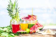 Ljusa nya sunda fruktsafter, frukt, ananas, vattenmelon på bakgrunden av havet Sommar vilar, den sunda livsstilen Arkivfoto