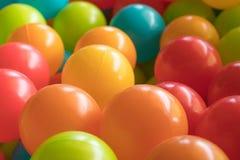 Ljusa och färgrika plast- leksakbollar, bollgrop, slut upp royaltyfria bilder