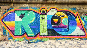 Ljusa och saftiga grafitti av ordet RIO DE JANEIRO på väggen på den soliga dagen i Ipanema sätter på land arkivfoton