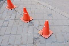 Ljusa orange trafikkottar som i rad står på asfalt Royaltyfria Foton