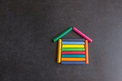 Ljusa pastellfärgade färgpennor är ordnade i formen av ett hus på a Royaltyfri Fotografi