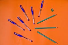 Ljusa pennor och blyertspennor på orange bakgrund royaltyfri fotografi