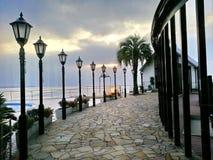 Ljusa poler på banan leder till havet med cloundy himmel Arkivfoton