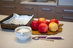 Ljusa röda äpplen i köket, bakplåt med folie för baki Royaltyfria Bilder
