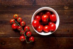 Ljusa röda saftiga tomater i en bunke på trä Royaltyfri Bild