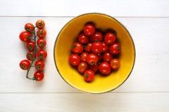 Ljusa röda saftiga tomater i en gul bunke på trä Royaltyfri Foto