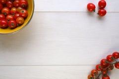 Ljusa röda saftiga tomater i en gul bunke på trä Royaltyfri Fotografi