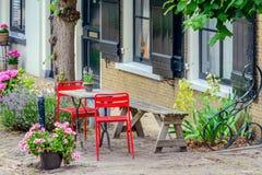 Ljusa röda stolar framme av ett historiskt holländskt hus Royaltyfria Bilder