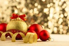 Ljusa röda struntsaker för jul med guld- band Royaltyfri Foto