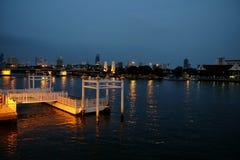 Ljusa reflexioner för stad över floden på natten Arkivfoton