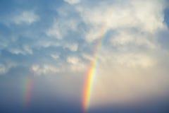 Ljusa regnbågar som dansar i ljusa luftiga moln över och dimmig himmel Royaltyfria Bilder