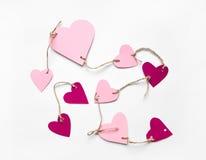 Ljusa rosa färger skyler över brister hjärtor förbindelse med ett rep för dag för valentin` s Lägenheten lägger på vit bakgrund Royaltyfri Foto