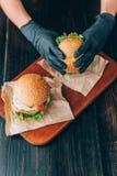 Ljusa saftiga aptitretande hamburgare med en kotlett, ost, marinerade gurkor, tomater och bacon i händerna av en flicka, en flick Royaltyfria Foton