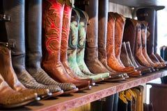 Ljusa skinande cowboykängor som står på en hylla i hantverk, shoppar royaltyfria foton