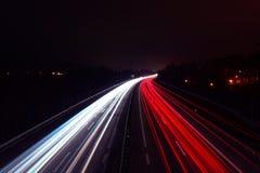 Ljusa slingor av bilar på natten på en huvudväg arkivfoto