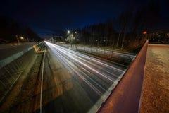 Ljusa slingor från bilar på Kehä 1 på Helsingfors fångade på natten med den mycket breda vinkellinsen och lång exponerin arkivfoton