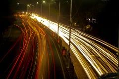 Ljusa slingor trafikerar slutareväggatan royaltyfria foton
