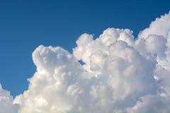 Ljusa soliga moln mot blå himmel för middagar fotografering för bildbyråer